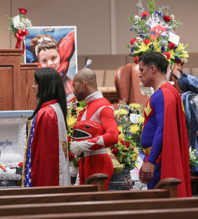 . Katie Olvera, left, dressed as Wonder Woman, Aaron Sloan, middle, of Seneca, dressed as a Power Ranger, and John Suber, right, of Greenville, dressed as Superman, pay their respects during a wake service for Jacob Hall, at Oakdale Baptist Church, Tuesday, Oct. 4, 2016 in Townville, S.C. Townspeople and classmates filled a church Tuesday evening to say goodbye to Jacob Hall, a 6-year-old boy who died in a school shooting, filing past a casket adorned with large photos, balloons and a life-size figure of one of his favorite superheroes, Batman.(Ken Ruinard/The Independent-Mail via AP, Pool)