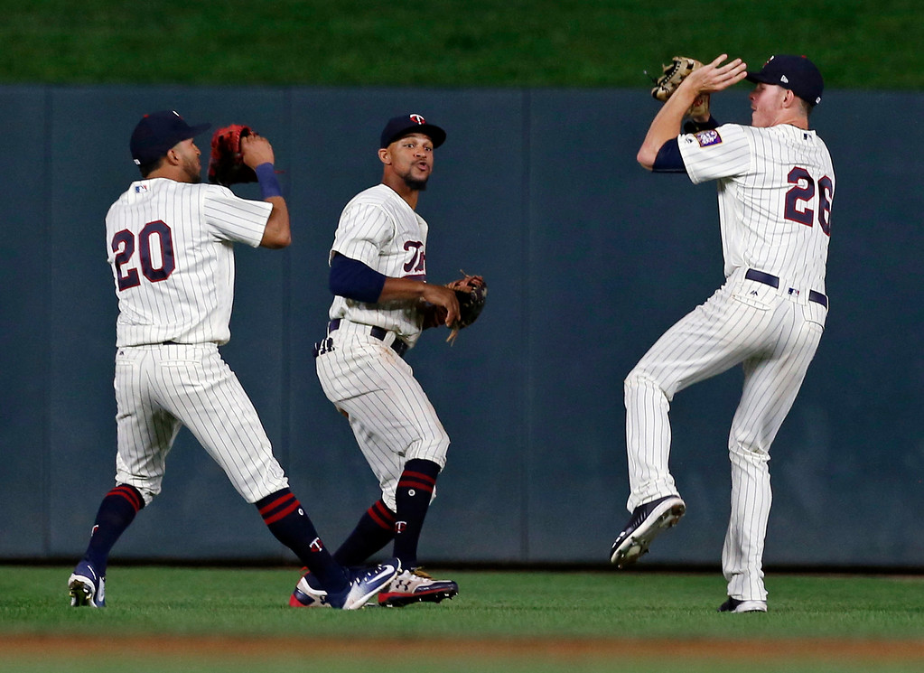 . Minnesota Twins outfielders, from left, Eddie Rosario, Byron Buxton and Max Kepler celebrate the Twins\' 4-2 win over the Cleveland Indians in the second game of a baseball doubleheader Thursday, Aug. 17, 2017, in Minneapolis. (AP Photo/Jim Mone)