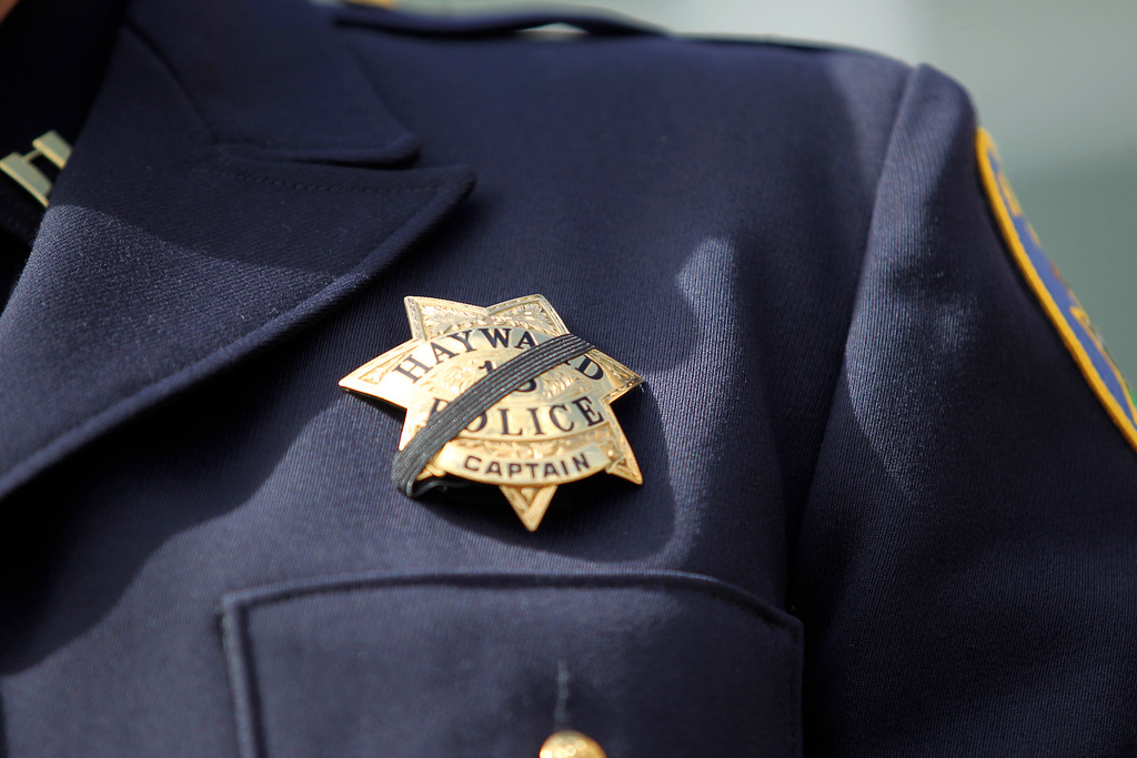 . Hayward Police Captain Mark Koller wears a black ribbon over his badge while speaking during a news conference outside city hall in Hayward, Calif., Wednesday, July 22, 2015. Koller confirmed that fellow officer Sgt. Scott Lunger was shot and killed during a traffic stop early Wednesday morning near Lion and Myrtle Streets. (Anda Chu/Bay Area News Group)