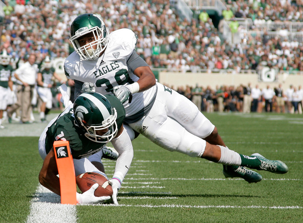 . Michigan State receiver A.J. Troup, left, dives for a touchdown against Eastern Michigan\'s Jason Beck during the second quarter of an NCAA college football game, Saturday, Sept. 20, 2014, in East Lansing, Mich. (AP Photo/Al Goldis)