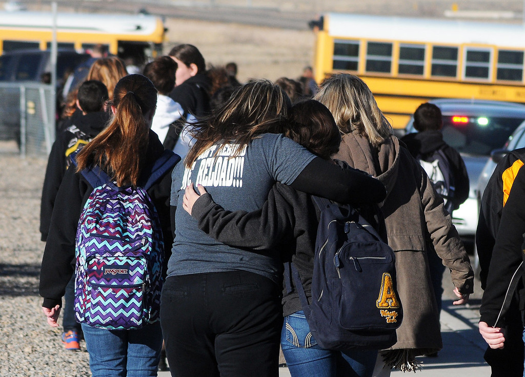 . Students are escorted from Berrendo Middle School after a shooting incident, Tuesday, Jan. 14, 2014, in Roswell, N.M. Roswell police said the suspected shooter was arrested at the school, but authorities have not said if there were any injuries. The school has been placed on lockdown. No other details are yet available. (AP Photo/Roswell Daily Record, Mark Wilson)