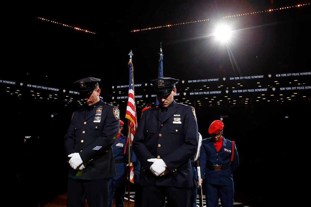 . New York Police Department officers Mark Cava, left, and Jason Muller participate in a moment of silence for two slain NYPD officers before an NBA basketball game between the Brooklyn Nets and the Detroit Pistons Sunday, Dec. 21, 2014, in New York.  A gunman ambushed NYPD officers Rafael Ramos and Wenjian Liu in Brooklyn Saturday, fatally shooting them as they sat in their patrol car before running into a nearby subway station and killing himself. (AP Photo/Jason DeCrow)