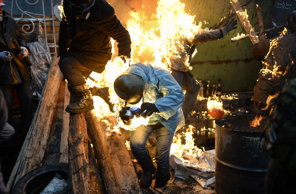 ". Protesters catch fire as they stand behind burning barricades during clashes with police on February 20, 2014 in Kiev. Ukraine\'s embattled leader announced a ""truce\"" with the opposition as he prepared to get grilled by visiting EU diplomats over clashes that killed 26 and left the government facing diplomatic isolation. The shocking scale of the violence three months into the crisis brought expressions of grave concern from the West and condemnation of an \""attempted coup\"" by the Kremlin.  BULENT KILIC/AFP/Getty Images"