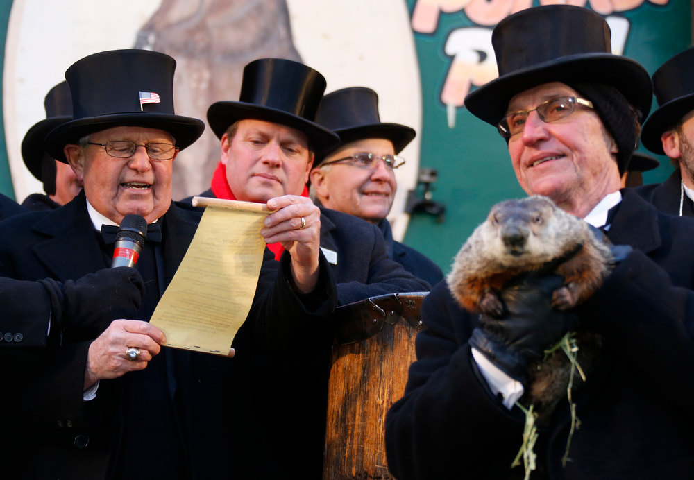 . Groundhog co-handler Ron Ploucha (R) holds Punxsutawney Phil as the Groundhog Club\'s Bob Roberts (L) reads the famous groundhog\'s annual weather prediction on Gobbler\'s Knob in Punxsutawney, Pennsylvania, on the 127th Groundhog Day, February 2, 2013. Phil did not see his shadow signaling an early end to winter. REUTERS/Jason Cohn