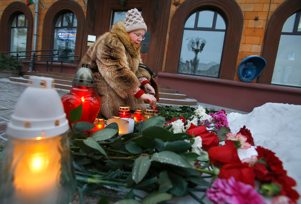 ". A woman lights a candle outside the French Embassy in Minsk, Belarus, Thursday, Jan. 08, 2015. French President Francois Hollande says the country has been ""struck in the heart\"" of its capital city in the attacks on a satirical newspaper. Masked gunmen stormed the offices of Charlie Hebdo on Wednesday, killing 12 people inside and out before fleeing. (AP Photo/Sergei Grits)"