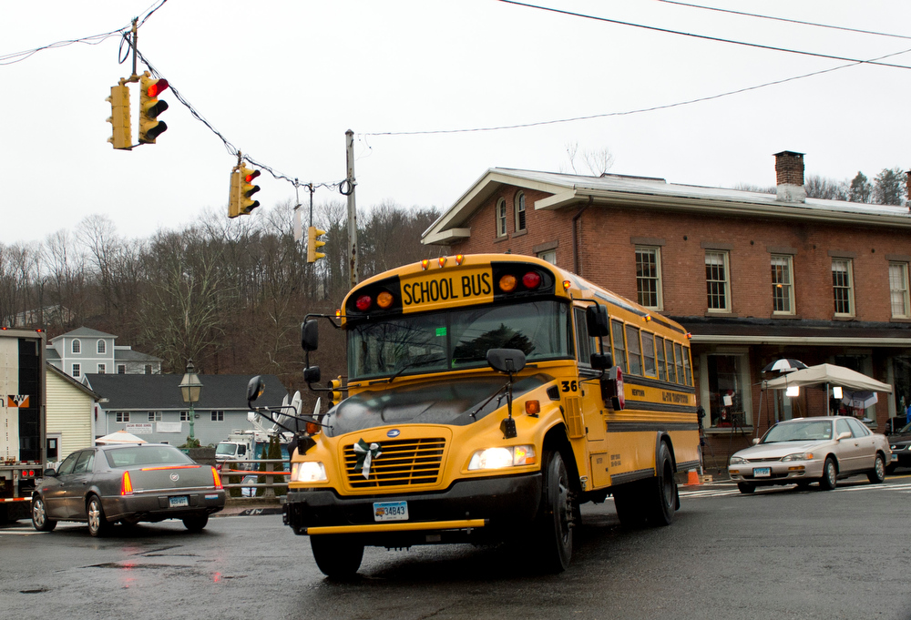 Description of . A school bus turns through an intersection December 18, 2012 in Newtown, Connecticut. Students in Newtown, excluding Sandy Hook Elementary School, return to school for the first time since last Friday's shooting at Sandy Hook which took the live of 20 students and 6 adults.  DON EMMERT/AFP/Getty Images