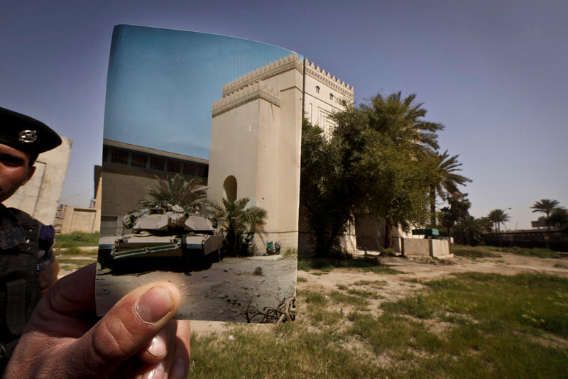 . Iraqi policeman Ahmed Naji stands on the grounds of the Iraqi National Museum at the site of a photograph showing a U.S. Army tank parked outside the Iraqi National Museum in Baghdad taken by Associated Press photographer Murad Sezer on Tuesday, May 6, 2003. Tens of thousands of artifacts chronicling some 7,000 years of civilization in Mesopotamia are believed to have been looted from Iraq in the chaos which followed the the US-led invasion in 2003. Despite international efforts to track items down, fewer than half of the artifacts have so far been retrieved. Photo taken on March 13, 2013. (AP Photo/Maya Alleruzzo)