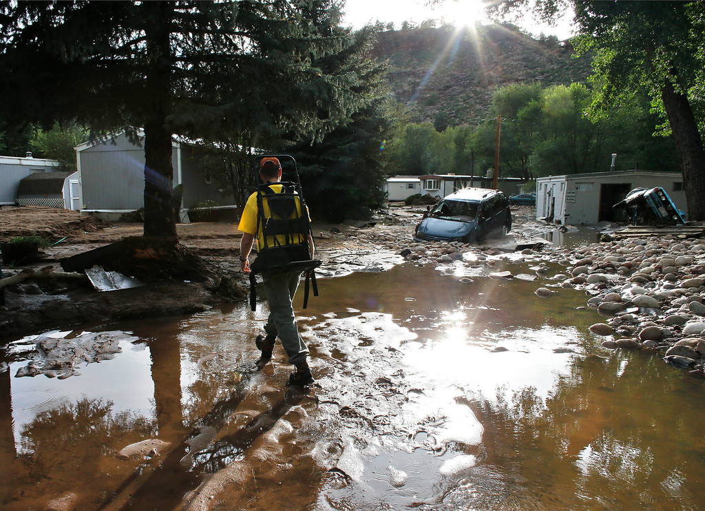 . Local resident Ben Rodman walks while helping a friend salvage her home after floods left homes and infrastructure in a shambles, in Lyons, Colo., Friday Sept. 13, 2013. (AP Photo/Brennan Linsley)