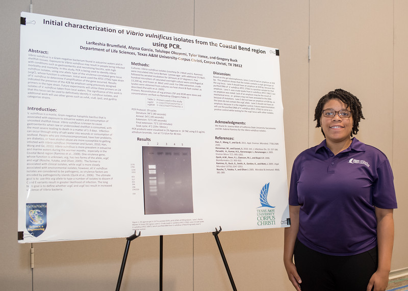 McNair Scholar LarReshia Brumfield stands next to her poster for the TRIO McNair Poster Presentation.