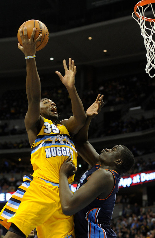 . Denver forward Kenneth Faried (35) went hard to the hoop against Charlotte center DeSafana Diop (2) in the second half. The Denver Nuggets defeated the Charlotte Bobcats 110-88 at the Pepsi Center Saturday night, December 22, 2012.  Karl Gehring/The Denver Post