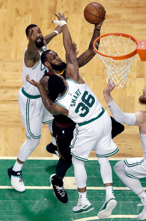 . Cleveland Cavaliers forward LeBron James, center, drives between Boston Celtics forward Marcus Morris, left, and uard Marcus Smart (36) during the first half in Game 7 of the NBA basketball Eastern Conference finals, Sunday, May 27, 2018, in Boston. (AP Photo/Charles Krupa)