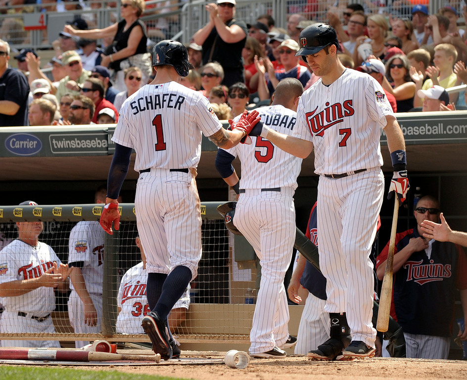 . Minnesota Twins\' Joe Mauer (7) greets teammates Eduardo Escobar, center, and Jordan Schafer (1) at their dugout after they scored during the third inning of a baseball game against the Detroit Tigers in Minneapolis, Sunday, Aug. 24, 2014. (AP Photo/Tom Olmscheid)