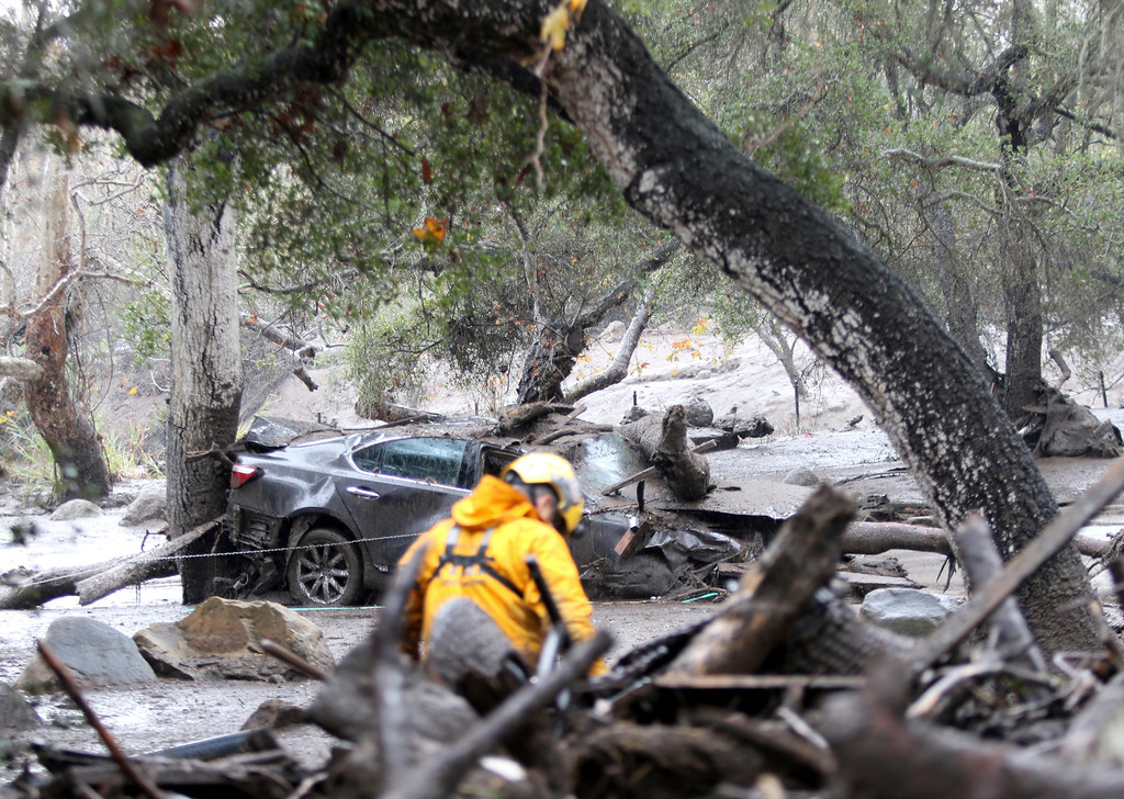 . A member of the Long Beach Search and Rescue team looks for survivors in Montecito, Calif. on Tuesday, Jan. 9, 2018. Several homes were swept away before dawn Tuesday when mud and debris roared into neighborhoods in Montecito from hillsides stripped of vegetation during a recent wildfire. (Daniel Dreifuss)