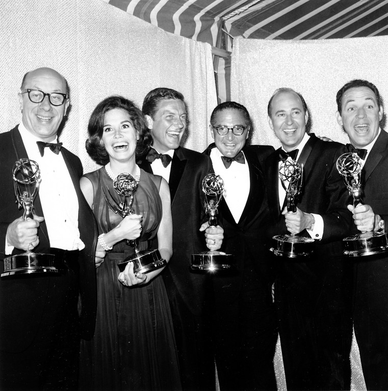 ". Participants in the television comedy series ""The Dick Van Dyke Show\"" pose with their awards at the 16th Annual Emmy Awards in Hollywood, Ca. on May 25, 1964. Left to right are: Richard Deacon; Mary Tyler Moore, Outstanding Continued Performance by an Actress in a Series, Lead; Dick Van Dyke, Outstanding Continued Performance by an Actor in a Series, Lead; Sheldon Leonard, producer of the show, which was named best comedy series; Carl Reiner, Outstanding Writing Achievement in a Series; and Jerry Paris, Outstanding Directorial Achievement in Comedy. (AP Photo)"