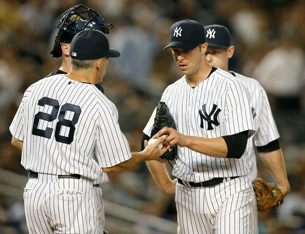 . New York Yankees starting pitcher Chris Capuano hands the ball to Yankees manager Joe Girardi (28) after pitching through six and two-thirds innings in a baseball game at Yankee Stadium in New York, Wednesday, Aug. 6, 2014.  (AP Photo/Kathy Willens)