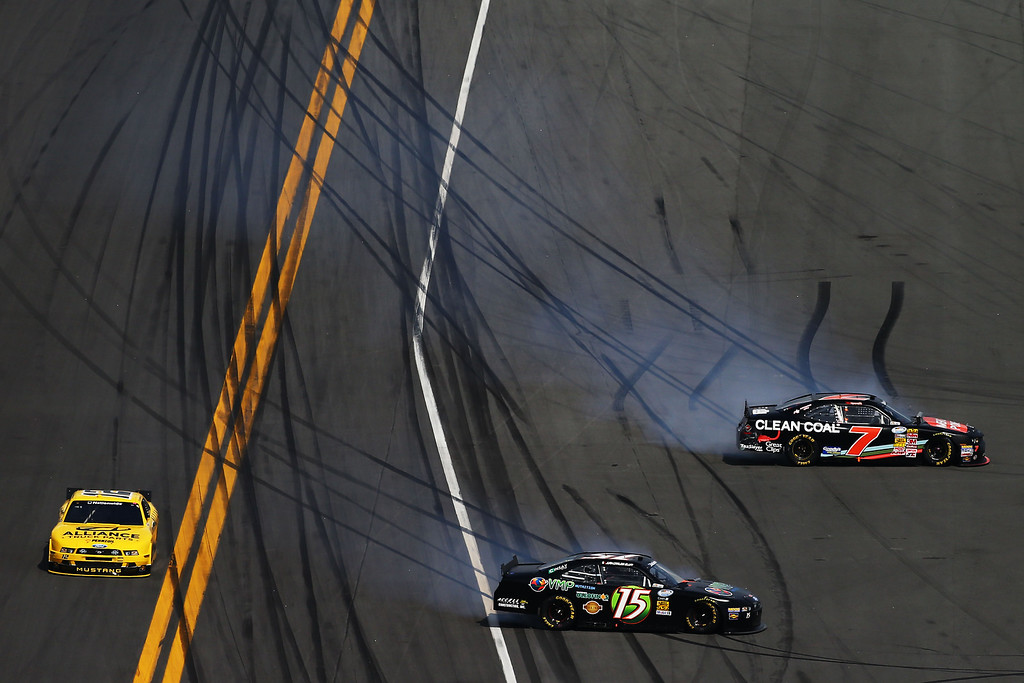. DAYTONA BEACH, FL - FEBRUARY 23:  Regan Smith, driver of the #7 Clean Coal Chevrolet, and Juan Carlos Blum, driver of the #15 VMP Ford, are involved in an incident during the NASCAR Nationwide Series DRIVE4COPD 300 at Daytona International Speedway on February 23, 2013 in Daytona Beach, Florida.  (Photo by Jonathan Ferrey/Getty Images)