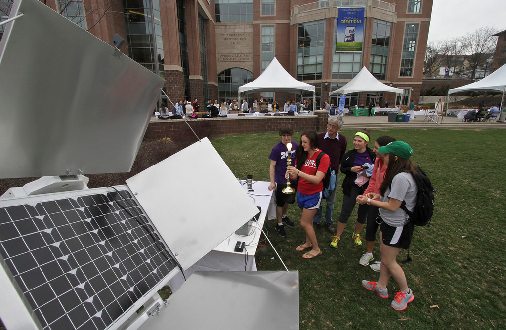 """. University of Scranton physics and electrical engineering lab manager Jim Loven shows students an \""""Off the Grid\"""" solar energy system used to charge a battery and operate an household lamp during Earth Day festivities at the school, Tuesday, Apriul 22, 2014, in Scranton, Pa.  From left are: Tyler Mulvihill, of Wilkes Barre; Isabella Dolente, Haddon Heights, NJ; Jim Loven, Chloe Strickland, of Scranton; Jackie Pesavento, Clarks Summit and Caroline Korz, of Havertown. (AP Photo/Scranton Times & Tribune, Michael J. Mullen)"""