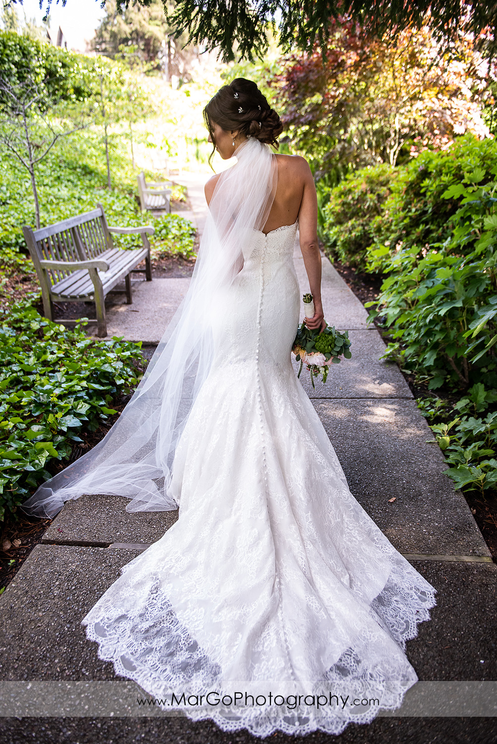 full body back portrait of bride holding flowers at Piedmont Park