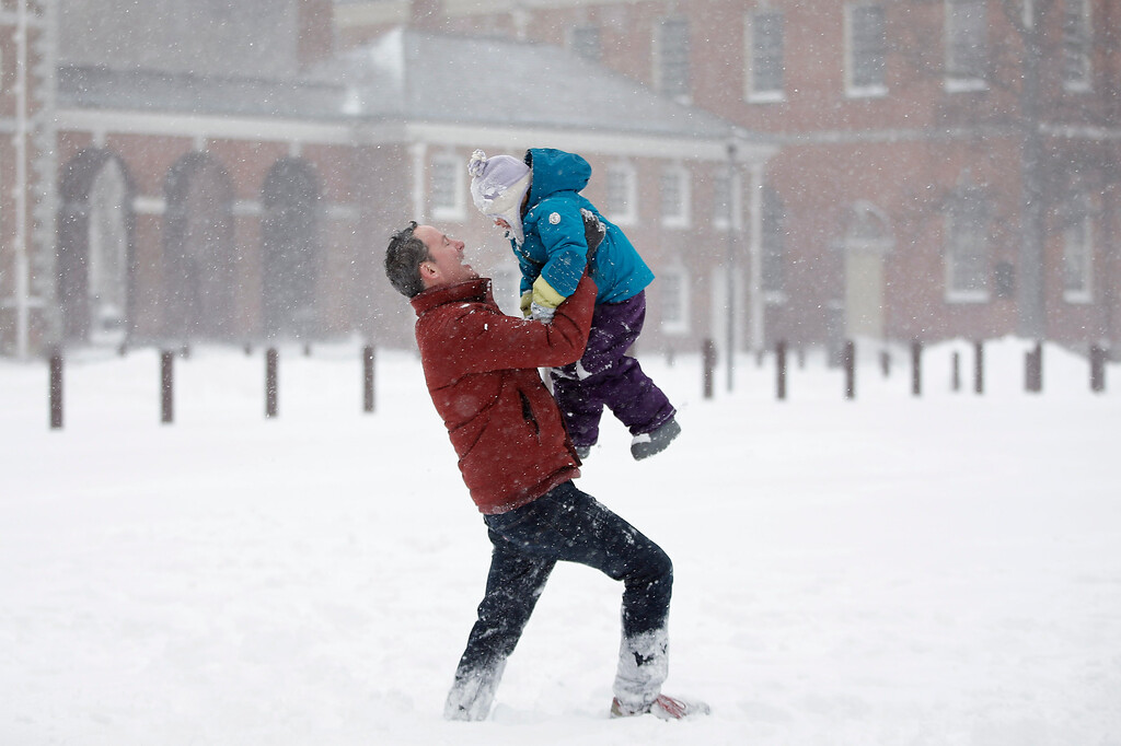 . Dan Rafalin, left, lifts his daughter, Delila Rafalin, 5, while playing in heavy snowfall with their family on Independence Mall, Saturday, Jan. 23, 2016, in Philadelphia. (AP Photo/Matt Slocum)