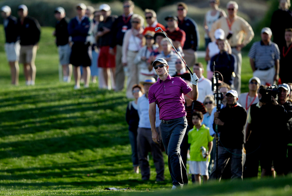 . Justin Rose of England follows his ball on the 18th hole during the first round of Abu Dhabi Golf Championship in Abu Dhabi, United Arab Emirates, Thursday, Jan. 17, 2013. (AP Photo/Kamran Jebreili)