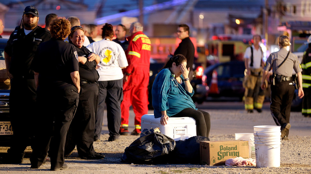 . A woman puts her hand over her face as she sits on a cooler in an area for first responders working a massive fire at the Seaside Park boardwalk, Thursday, Sept. 12, 2013, in Seaside Park, N.J. The fire, which apparently started in an ice cream shop and spread several blocks, hit the recently repaired boardwalk, which was damaged last year by Superstorm Sandy. There were no other early reports of any injuries. (AP Photo/Julio Cortez)