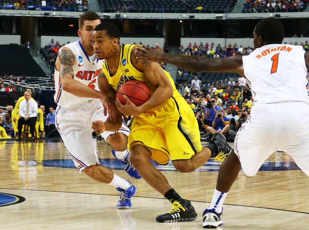 . Trey Burke #3 of the Michigan Wolverines drives between Scottie Wilbekin #5 and Kenny Boynton #1 of the Florida Gators in the first half during the South Regional Round Final of the 2013 NCAA Men\'s Basketball Tournament at Dallas Cowboys Stadium on March 31, 2013 in Arlington, Texas.  (Photo by Ronald Martinez/Getty Images)