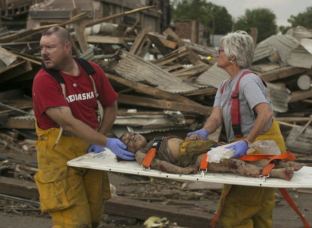 . Rescue personnel tend to a young tornado victim in  Pilger, Neb., Monday, June 16, 2014. A hospital spokeswoman says at least one person is dead and at least 16 more are in critical condition after two massive tornadoes swept through northeast Nebraska. (AP Photo/Mark \'Storm\' Farnik)