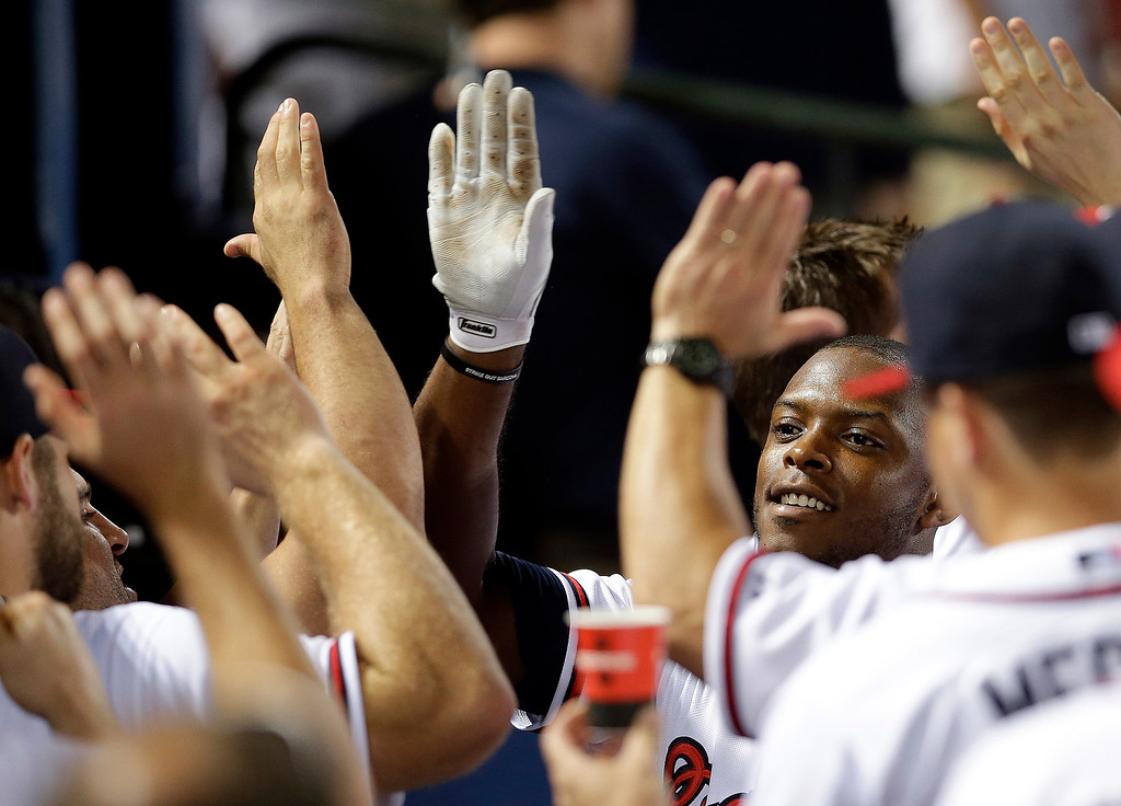 . Atlanta Braves\' Justin Upton (8) celebrates in the dugout after hitting a three-run home run in the eight inning of a baseball game against the Colorado Rockies in Atlanta, Thursday, Aug. 1, 2013. Upton hit two homers and the Braves won 11-2. (AP Photo/John Bazemore)