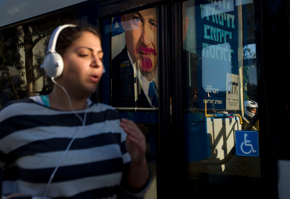 Description of . A woman jogs past a vandalized election campaign billboard of Israeli Prime Minister and Likud Party leader Benjamin Netanyahu that is reflected on a bus window in Tel Aviv, Israel, Monday, Jan. 21, 2013.  The general elections will be held on Tuesday, Jan. 22, 2013. (AP Photo/Ariel Schalit