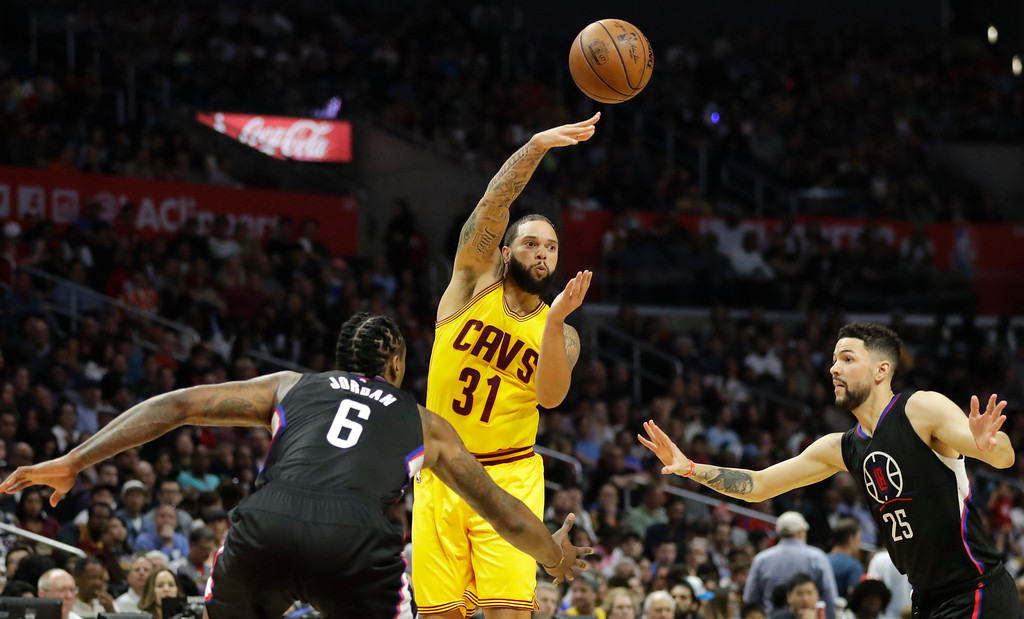 . Cleveland Cavaliers\' Deron Williams, center, passes the ball under defense by Los Angeles Clippers\' Austin Rivers, right, and DeAndre Jordan during the second half of an NBA basketball game Saturday, March 18, 2017, in Los Angeles. (AP Photo/Jae C. Hong)