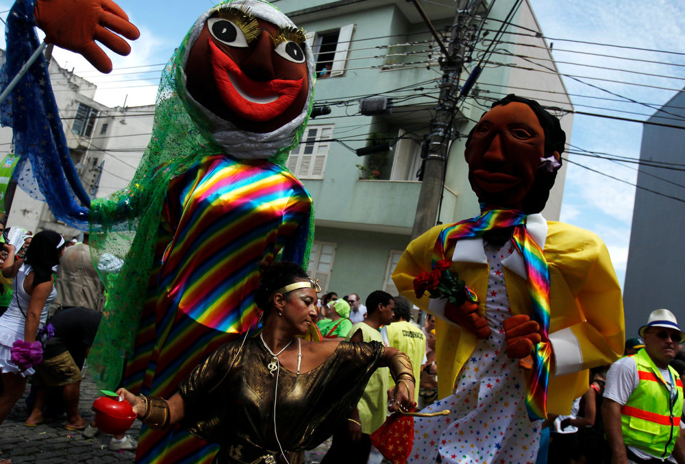 Description of . A reveller dances in front of puppets during the annual block party known as 'Carmelitas', one of the many carnival parties to take place in the neighbourhoods of Rio de Janeiro, February 8, 2013. REUTERS/Pilar Olivares
