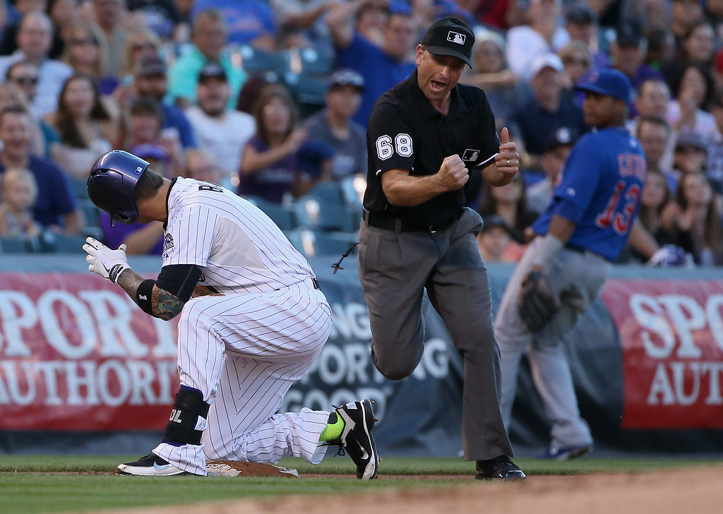 . DENVER, CO - AUGUST 05:  Umpire Chris Guccione makes the call as Brandon Barnes #1 of the Colorado Rockies is tagged out at third by third baseman Luis Valbuena #24 of the Chicago Cubs trying to stretch his two RBI double in the second inning at Coors Field on August 5, 2014 in Denver, Colorado.  (Photo by Doug Pensinger/Getty Images)