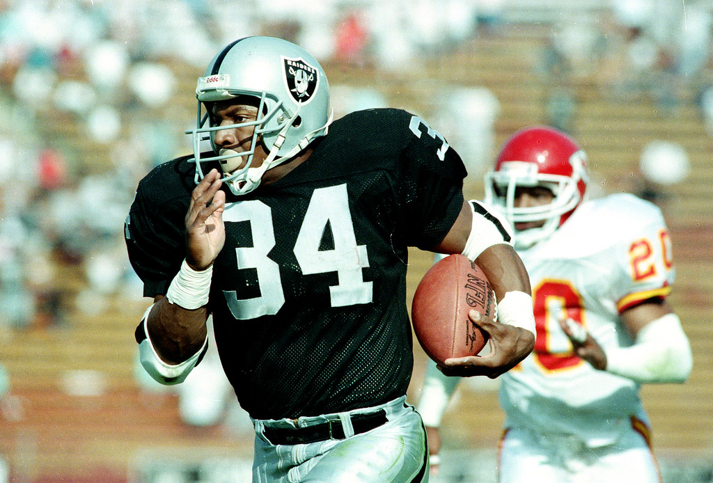 . Bo Jackson, the two-sport star and running back for the Los Angeles Raiders, takes off on a 45-yard run against the Kansas City Chiefs, including free safety Deron Cherry (20), early in the fourth quarter of Sunday, October 15, 1989 game at the Coliseum in Los Angeles. (AP Photo/Bob Galbraith)