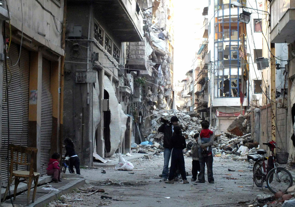 . Children talk to a boy holding a weapon in a damaged street in Homs March 25, 2013. Picture taken March 25, 2013. REUTERS/Yazan Homsy