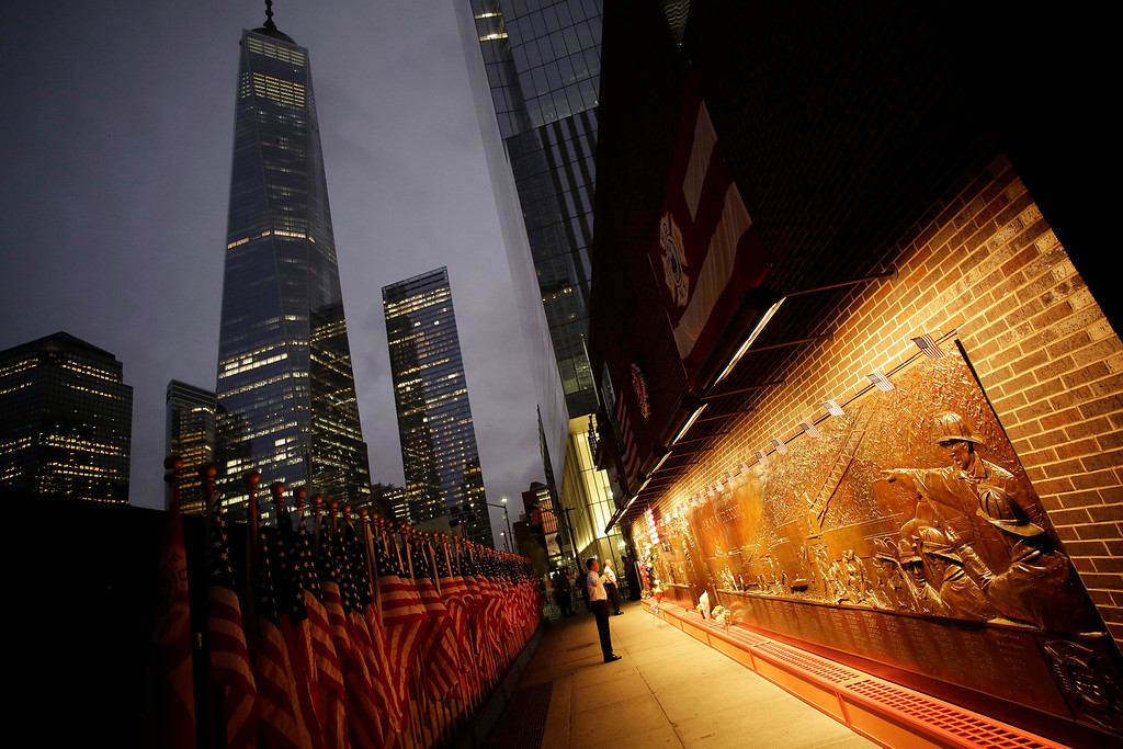 . A firefighter looks at a memorial mural on the outside of firehouse Engine 10 Company 10 adjacent to the World Trade Center in New York, Thursday, Sept. 11, 2014. Three hundred forty three New York firefighters were killed in the terrorist attacks of Sept. 11, 2001. (AP Photo/Mark Lennihan)