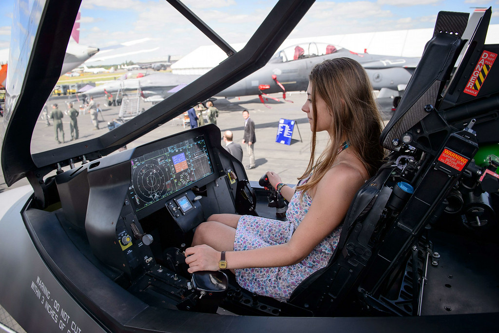 . Physics student Katie Ley from Farnborough sits in a mock-up of the Lockheed Martin F-35 Lightning II cockpit at the Farnborough air show in Hampshire, England, on July 14, 2014. The biennial event sees leading companies from the aviation industry showcase their latest technology. The week-long Farnborough airshow opened under a cloud however owing to the absence of the stricken US-built F-35 stealth fighter jet. The F-35, which was grounded in the United States last week because of an engine fire, will not appear as planned on the airshow\'s first day but might still take part at the end of the week, organisers said.  AFP PHOTO / LEON  NEAL/AFP/Getty Images