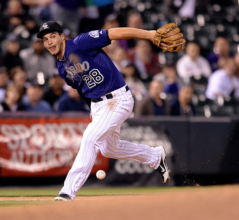. Colorado infielder Nolan Arenado dropped the ball trying to throw out Chicago batter Dayan Vidiedo in the eighth inning. The Colorado Rockies hosted the Chicago White Sox Tuesday night, April 8, 2014 at Coors Field in Denver.  (Photo by Karl Gehring/The Denver Post)