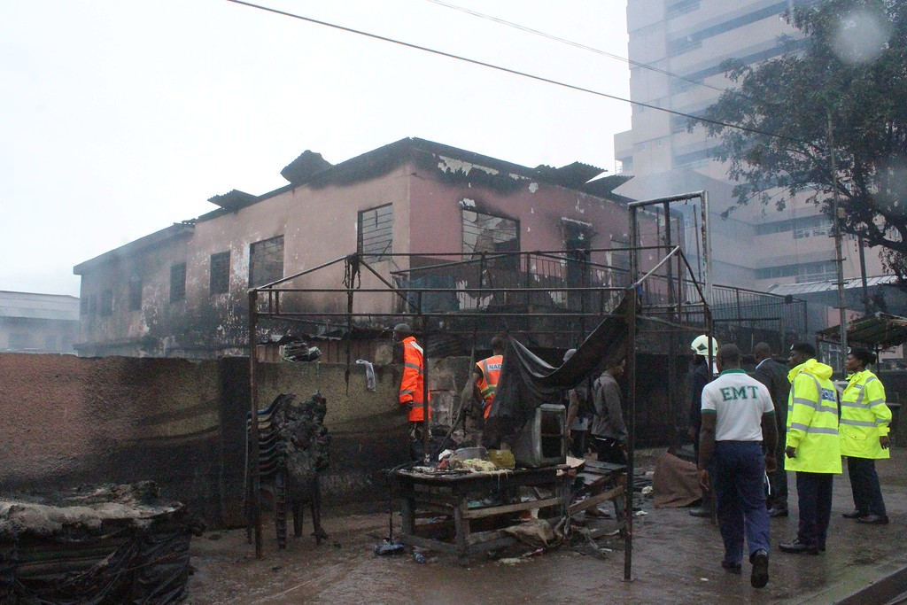 . Rescuers and officials look at a burnt-out house on the site where at least 90 people were killed in a petrol station fire in Ghana\'s capital, Accra, on June 4, 2015. The fire broke out at the filling station in the Kwame Nkrumah Circle area of the city late on Wednesday night and is thought to have spread from a nearby residence. AFP PHOTO / FATI BRAIMAH/AFP/Getty Images