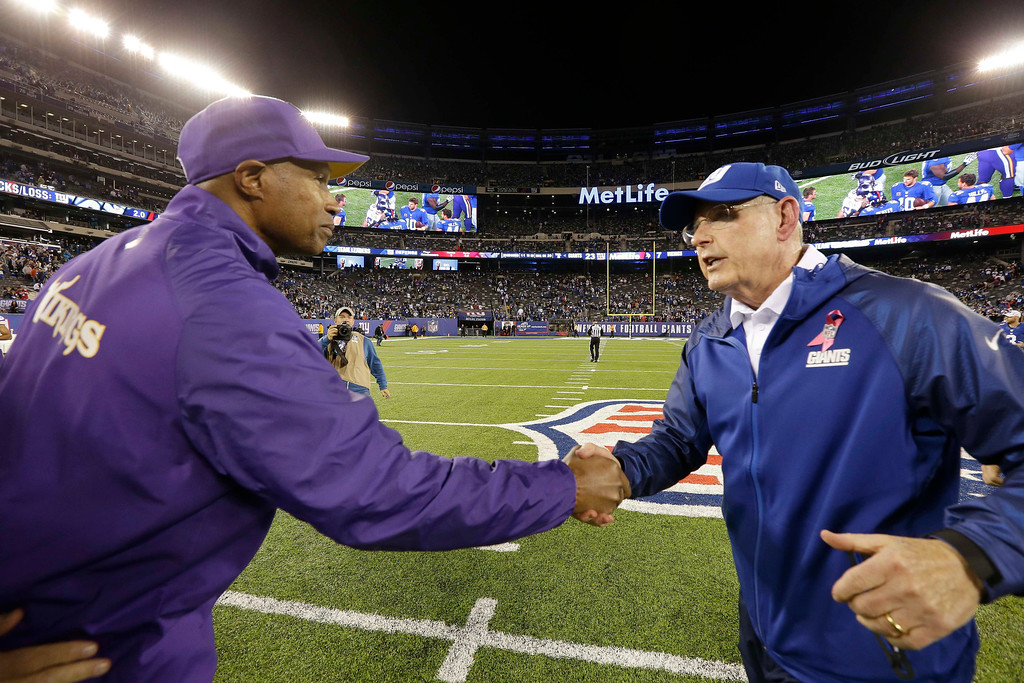 . Minnesota Vikings head coach Leslie Frazier, left, shakes hands with New York Giants head coach Tom Coughlin after an NFL football game Monday, Oct. 21, 2013 in East Rutherford, N.J. The Giants won the game 23-7. (AP Photo/Julio Cortez)