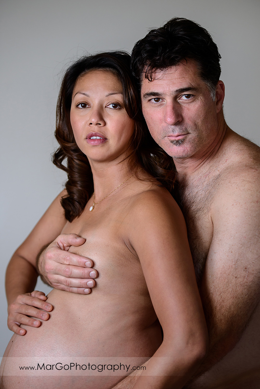 nude portrait of pregnant woman her husband looking into camera