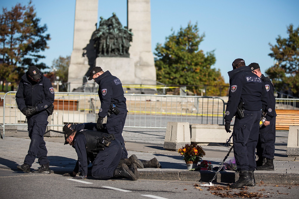 . Members of the Ottawa Police sweep the area in front of the National War Memorial one day after a lone gunman killed  Cpl. Nathan Cirillo of the Canadian Army Reserves, who was standing guard at the memorial, on October 23, 2014 in Ottawa, Canada.  (Photo by Andrew Burton/Getty Images)