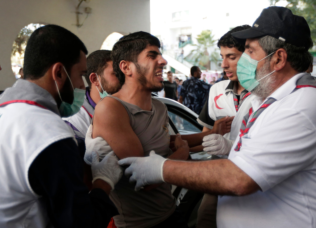 . Palestinians assist a youth, wounded in an Israeli strike, into the emergency room at Shifa Hospital, in Gaza City, northern Gaza Strip,Thursday, July 31, 2014. (AP Photo/Lefteris Pitarakis)