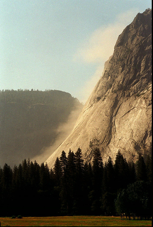 . Dust rises off Glacier Point in the aftermath of a small rock slide Thursday, July 11, 1996, in Yosemite National Park, Calif. A rockslide in the same area killed one person and injured six when the Happy Isles Nature Center was crushed by falling rocks. (AP Photo/Thor Swift)