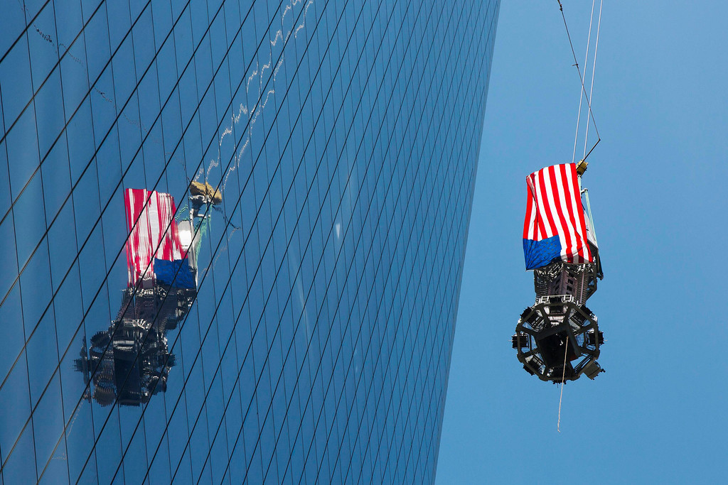 . A U.S. flag flutters in the wind as the final piece of a spire is lifted to the top of One World Trade Center in New York, May 2, 2013. REUTERS/Lucas Jackson