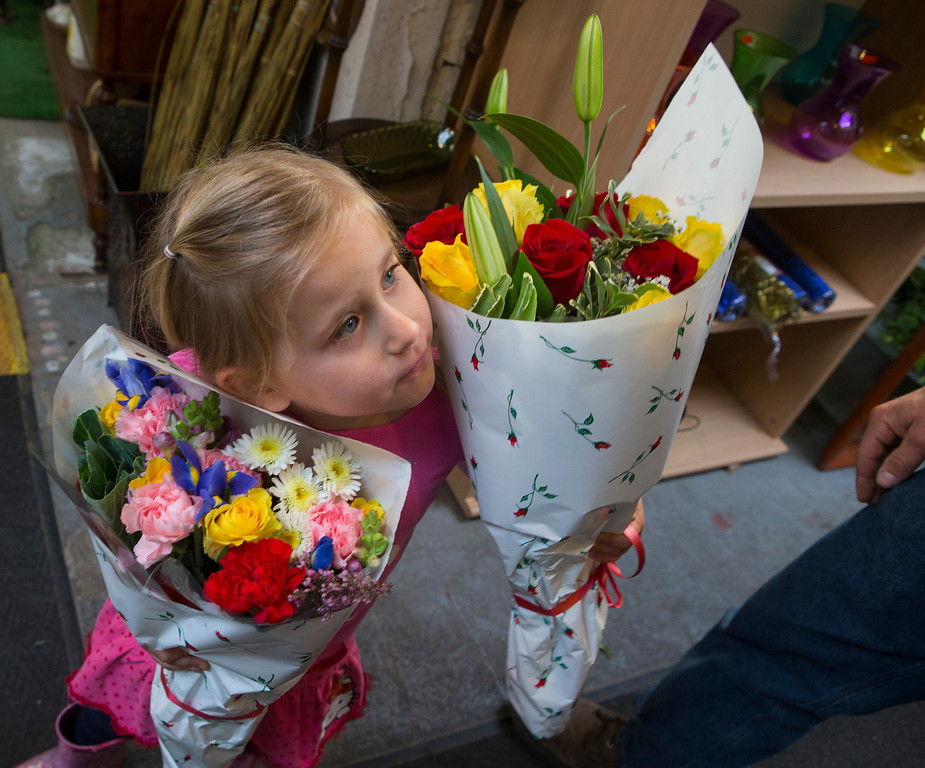 . Violet Holtz, 4, holds flowers for her dad Richard at Repetto\'s Greenhouse Florist and  in Half Moon Bay, Calif. on Wednesday, Feb. 13, 2013. Repetto\'s expects to be busy on Valentine\'s Day. (John Green/Staff)