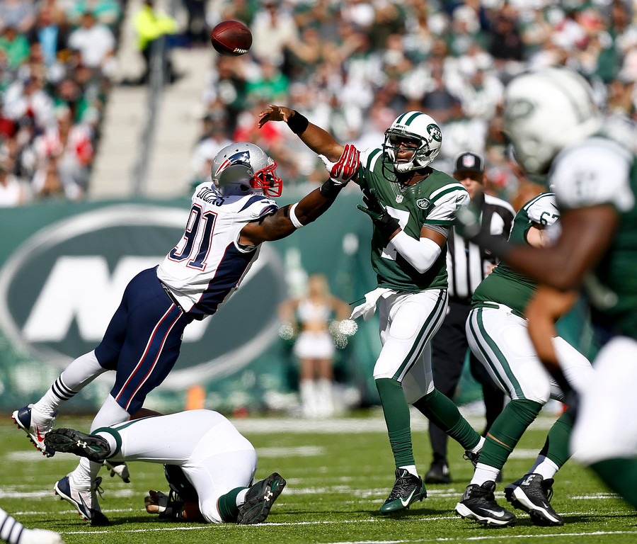 . Geno Smith #7 of the New York Jets passes under pressure from Jamie Collins #91 of the New England Patriots during their game at MetLife Stadium on October 20, 2013 in East Rutherford, New Jersey.  (Photo by Jeff Zelevansky/Getty Images)