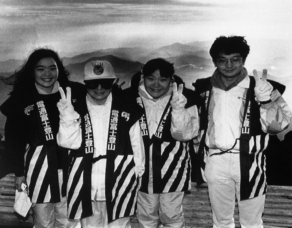 """. Yoko Ono, second from left, widow of John Lennon, signals her hopes for world peace in celebration of \""""Harmonic Convergence\"""" along with her two nieces and a nephew, from the top of Mount Fuji, Japan, on Monday, August 17, 1987.   Hiking overnight to the summit, Ms. Ono joined 25 other participants in witnessing the sunrise, the peak of the global celebration. (AP Photo/David Nelson)"""