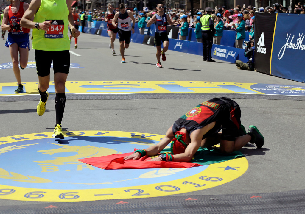 . Manuel Cabral, of Canada, kneels on a flag of Portugal, after finishing the 120th Boston Marathon on Monday, April 18, 2016, in Boston. (AP Photo/Elise Amendola)