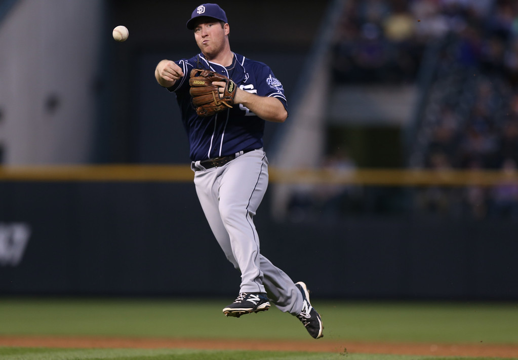 . San Diego Padres second baseman Jedd Gyorko throws to first base to put out Colorado Rockies\' Jore De La Rosa to end the third inning of a baseball game in Denver on Saturday, Sept. 6, 2014. (AP Photo/David Zalubowski)