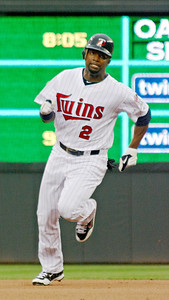 Denard Span heads for third with a triple - the first hit at Target Field